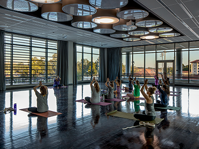 Photo of class participating in yoga with the blinds open.