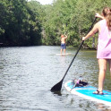 person paddleboarding on river
