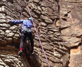 Photo of student in pink climbing rock