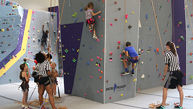 Photo of two UREC employees and multiple children on the climbing wall