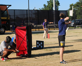 Photo of six students playing archerytag and two UREC employees on field behing UREC. Bus in background
