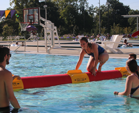 Photo of six students in outdoor pool playing on floating balance beam