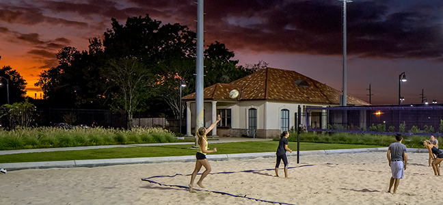 Photo of five students playing intramural outdoor volleyball as sun sets