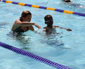 girl giving swimming lessons to child