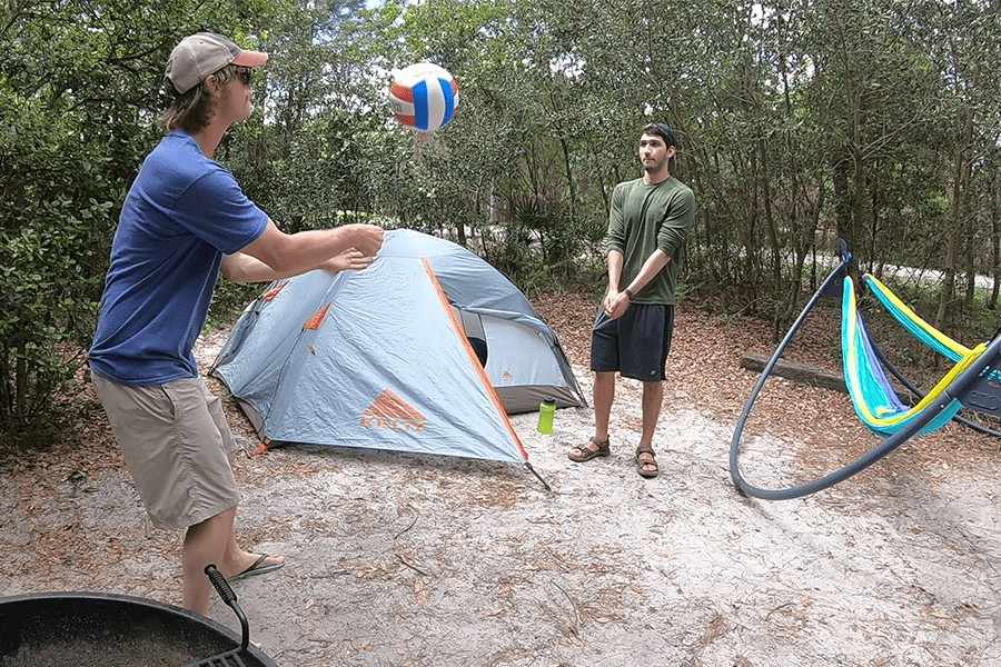 two men playing volleyball in the woods by a tent.