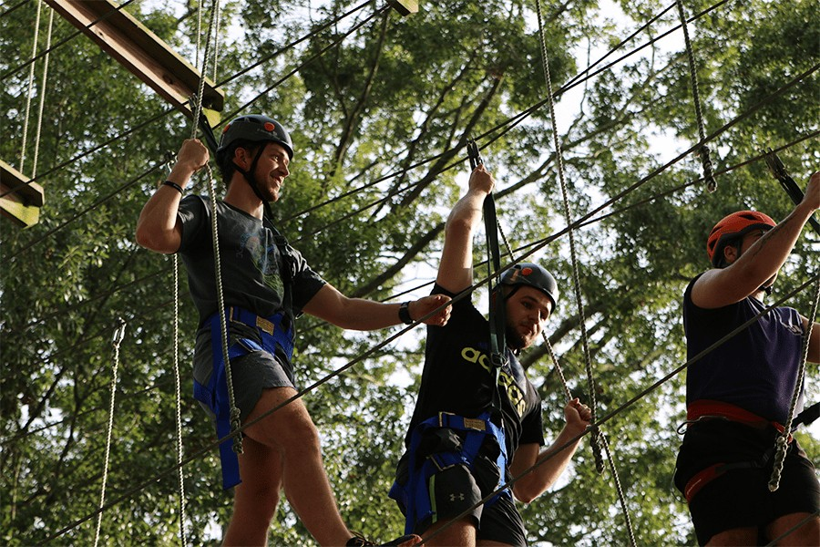 2 Males climbing on challenge course.