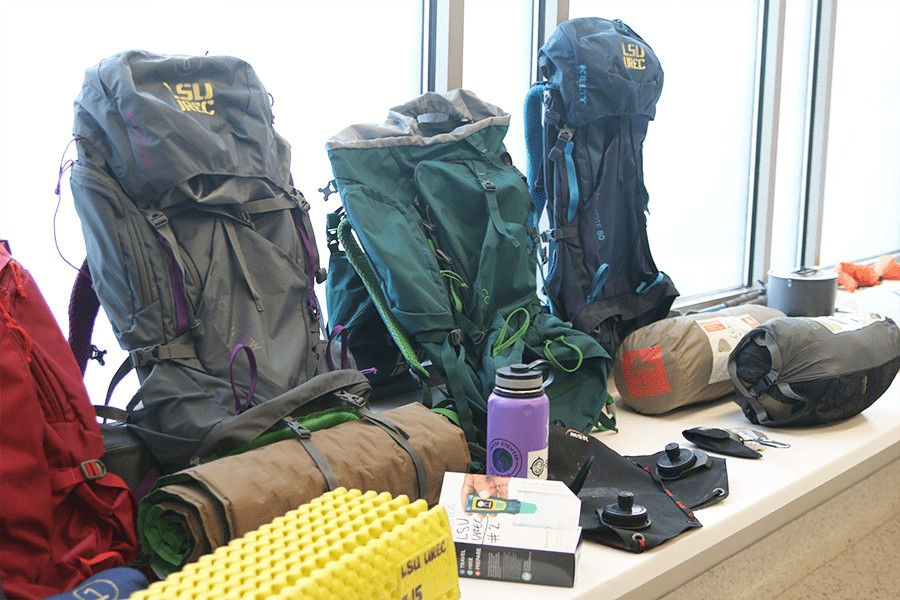 Backpacking gear leaning against a glass wall.