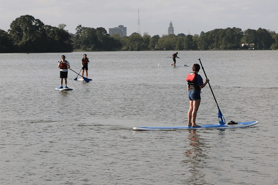 4 people on stand up paddle boards on LSU Lakes.