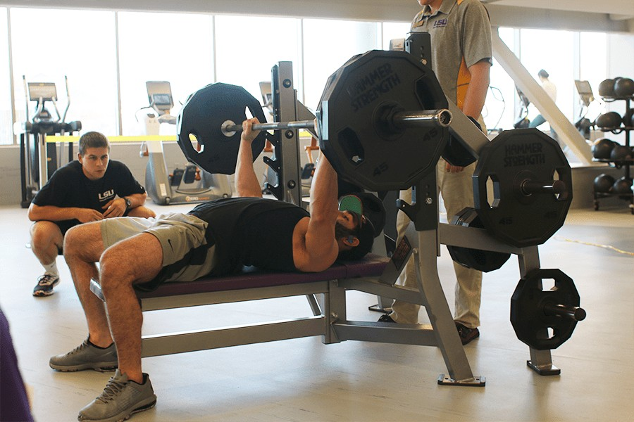 Male bench pressing with judge.