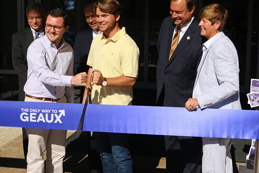 2 males cutting grand opening ribbon.