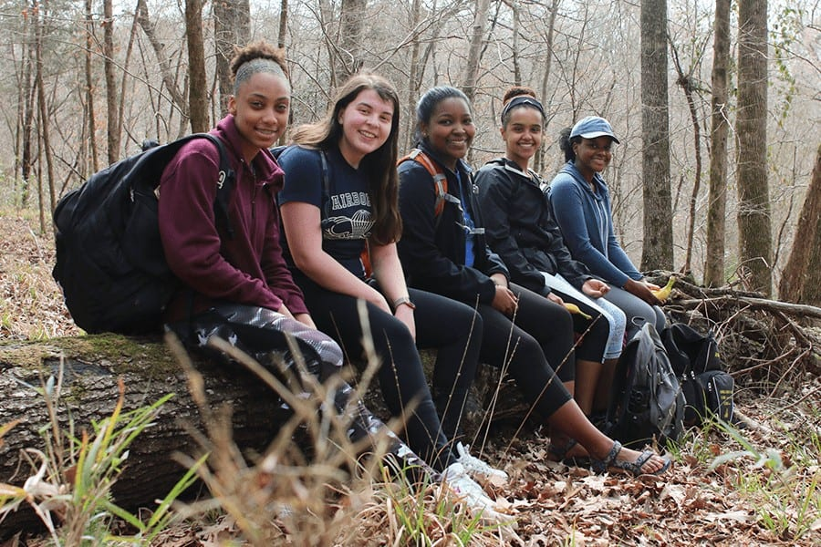 5 females sitting in the woods.