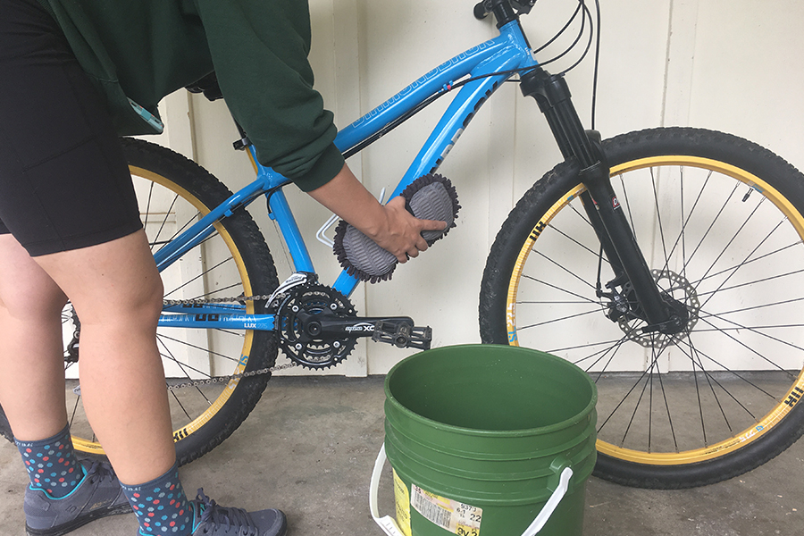 Photo of person cleaning a bike frame.