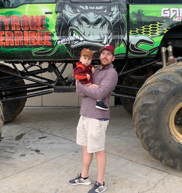 John with Win in front of monster truck.